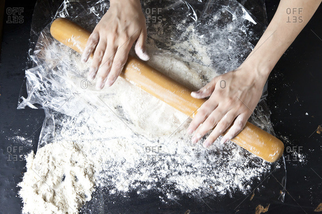 Action shot of hands preparing a pie on a floured surface.