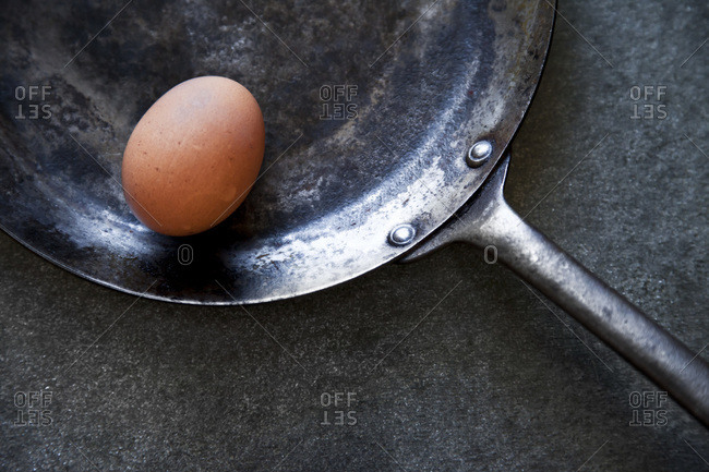 A frying pan with a fresh egg in its shell.