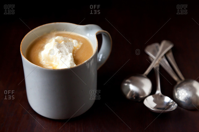 A cup of butter beer with whipped cream and a pile of spoons