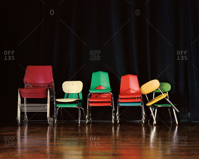 Vintage school chairs in front of a dark curtain