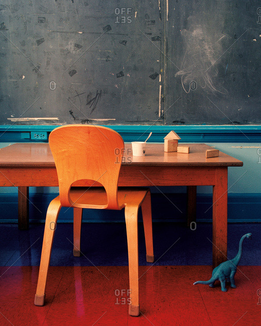 A table in a retro classroom with a toy dinosaur