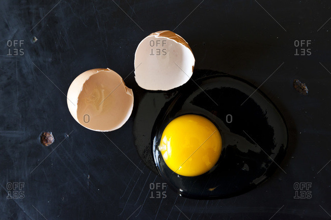 A cracked egg with intact yolk on a black surface