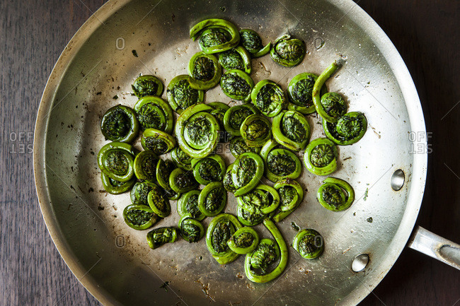 Fiddleheads cooked in a frying pan
