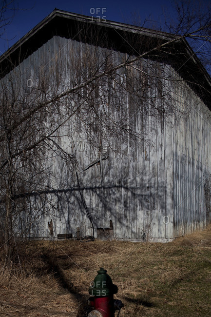 Trees shadow on side of barn with red fire hydrant