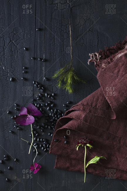 Dried black beans on charred black wood surface, maroon cloth, pink flower