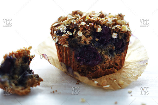 Blueberry muffin in paper wrapper, torn open, backlit, on white surface