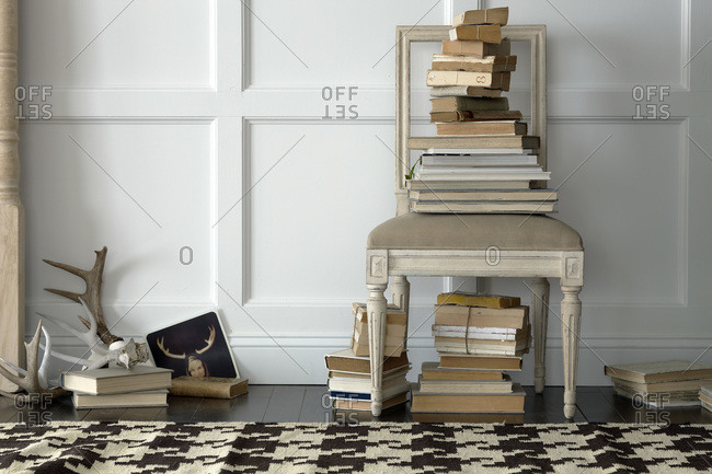 White Swedish chair against white wall, brown and cream herringbone rug, antlers and piles of books