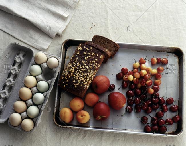 Dark brown bread, peaches, cherries, pale colored eggs on white rough cloth on  baking pan