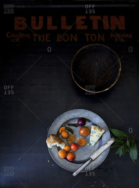 Still life of pewter plate with apricots, blue cheese, bay leaf, broken bread on dark surface with red letters that say bulletin.