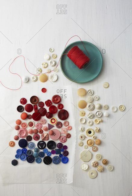 Still life of red, pink, blue and white buttons, aqua plate, red thread on wax paper and white wood surface