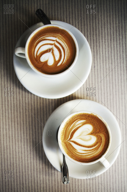 Two cappuccinos in white cups with saucers and spoons on striped cloth