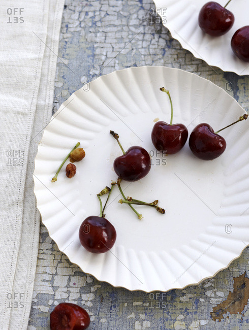 Cherries and pits with stems on paper plates on chipped blue wood surface and white cloth