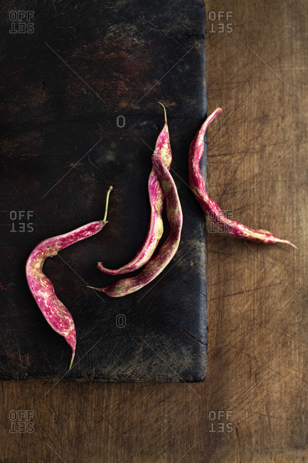 Four cranberry beans on dark brown cutting board on wood table