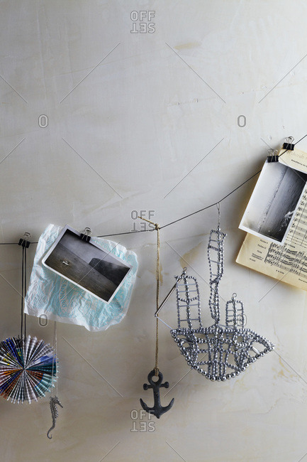String of objects hanging: vintage photos, anchor, rhinestone boat