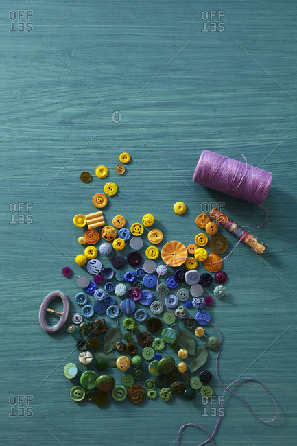 Yellow, blue and green buttons on aqua wood background with pink/violet thread