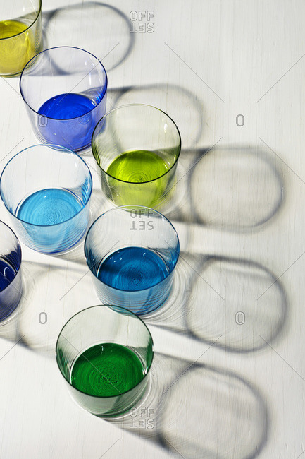 Reflections of seven glasses on white surface with blue, green, aqua and yellow tinted bottoms