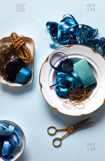 Blue ribbon, gold thread, twine, white plates rimmed in gold, gold scissors on light blue background