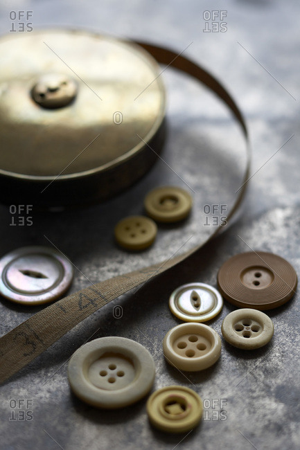 Still life of buttons and old, vintage brass measuring tape on metal surface
