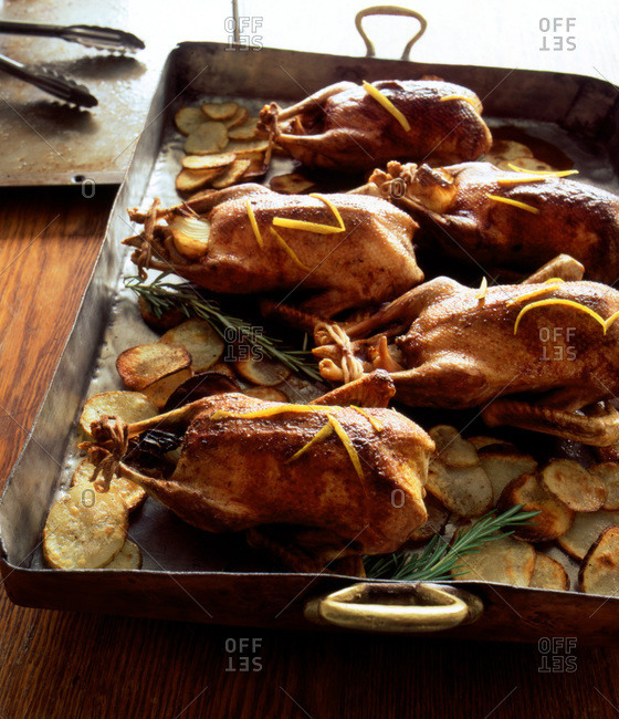 Five roasted ducks on copper pan with thin sliced potatoes and rosemary