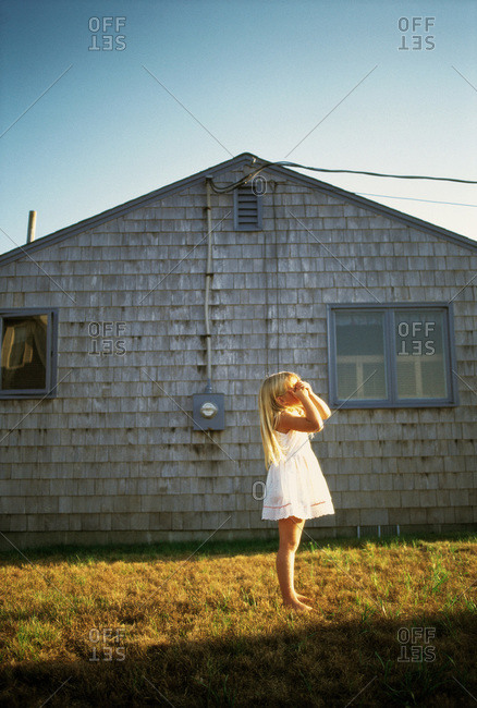 Little girl in white dress playing hide and seek in front of a small gray cottage in Maine