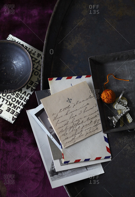 Collection of letter and photos on black metal tray with Eiffel tower key chain on crushed purple velvet fabric