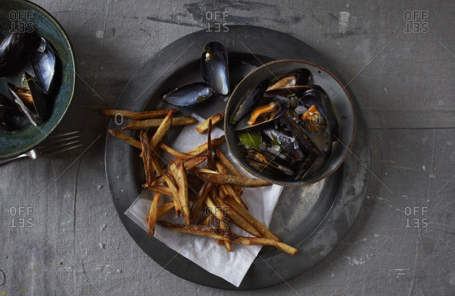 French fries and mussels on pewter plate on painter's drop-cloth