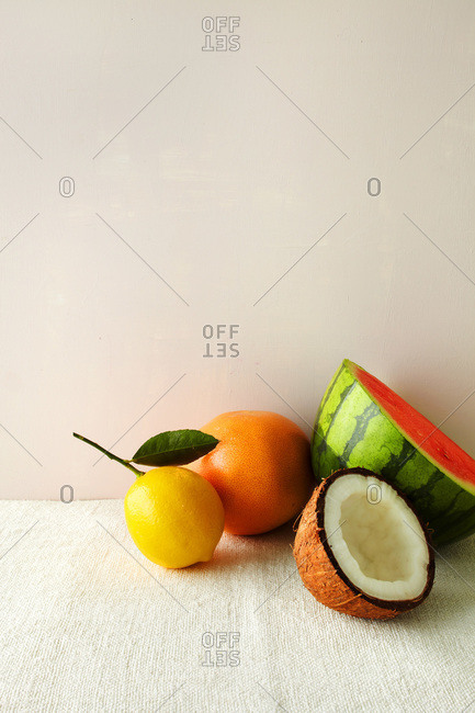 Watermelon, grapefruit, coconut and orange still life on white with pale pink background