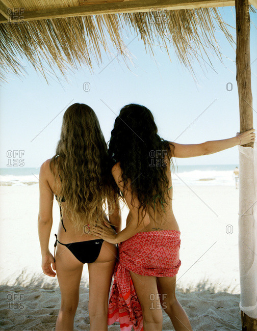 Two young women with long, wavy hair in bikinis under grass roof cabana on a beach