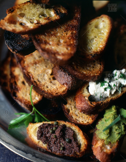 A pile of grilled bread slices with olive spread, capers and parsley