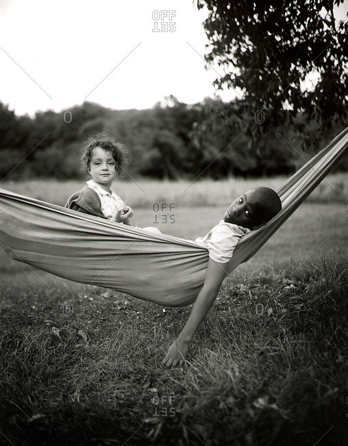 Black and white image of two young children in hammock