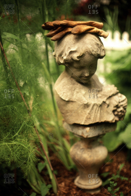 Garden statue of classical boys head with worn leather garden gloves on head