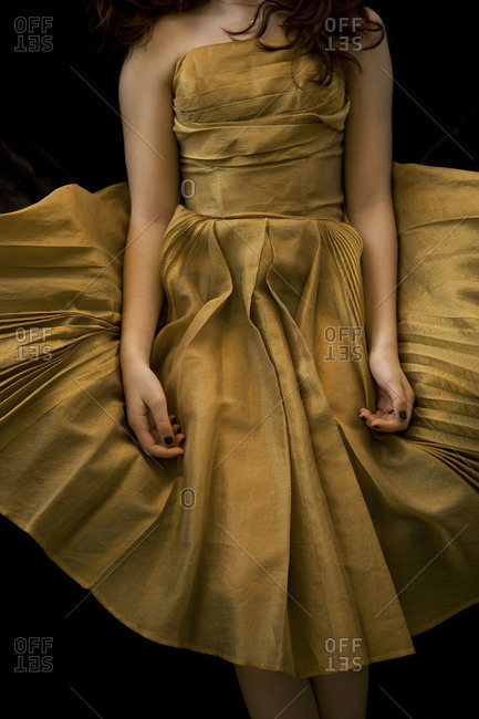 Young girl seen from neck down in vintage gold dress on black background