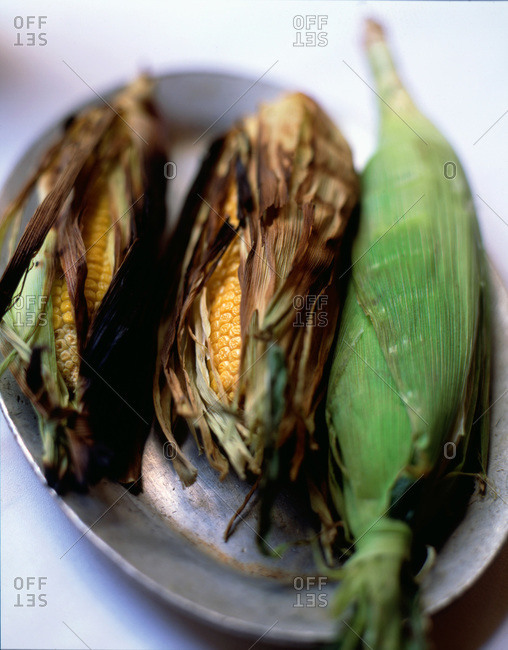 Three ears of corn grilled in husks on pewter plate
