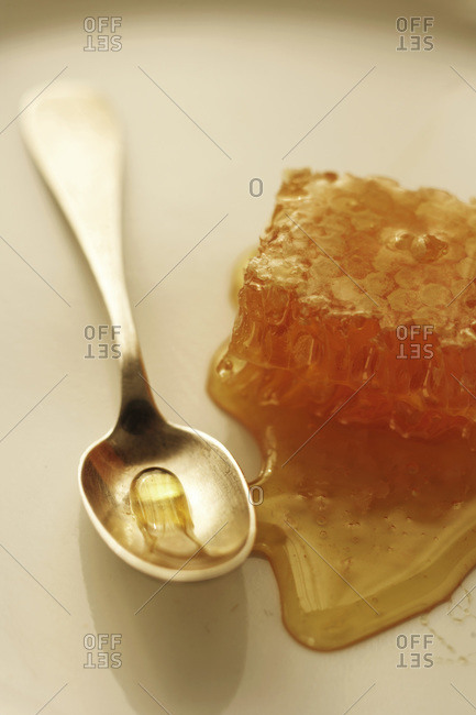 Comb of honey dripping honey onto a surface with silver spoon