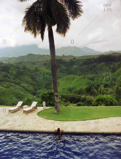 Girl leaning on side of pool with view of palm tree and mountains of Kauai in the distance