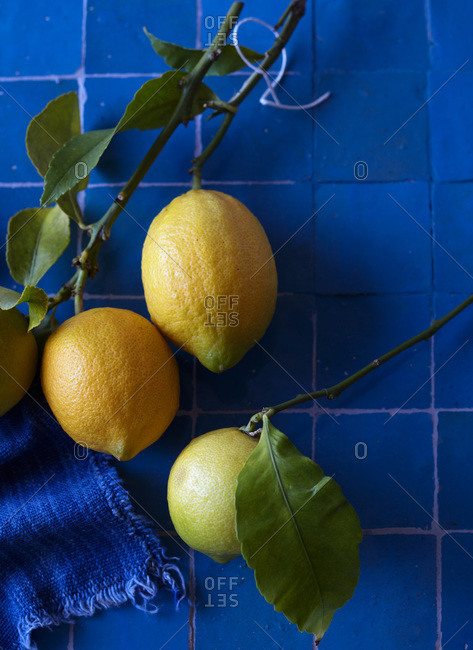 Yellow lemons with leaves on deep blue tile with blue cloth