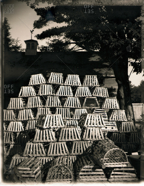Black and white image of stacks of old wooden lobster pots with roof-line and weather vane in background