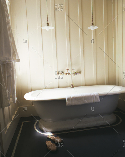 Old fashioned tub with slippers on gray floor and robe hanging on hook with two lamps over tub