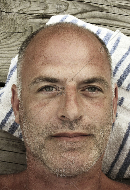 Close up portrait of bald, gray haired man resting his head on striped white and blue pillow on dock seen from above.