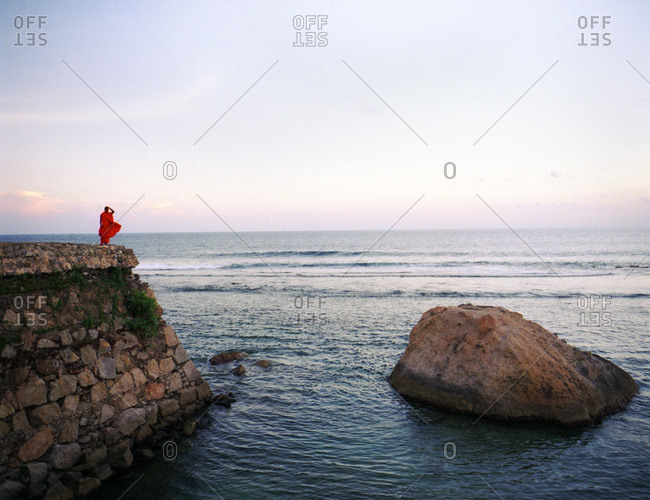 View over harbor in Sri Lanka with lone monk in red robes blowing in wind on cliff