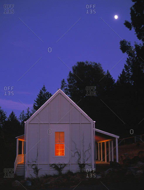 Small white house at dusk with one window and porch lights glowing orange with moon in violet blue sky