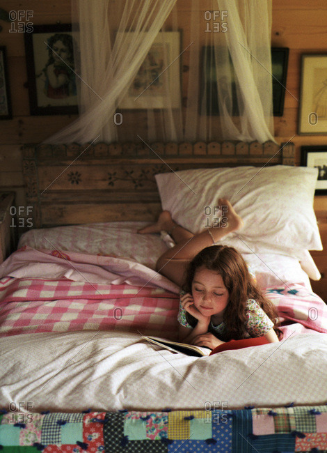 Young red headed girl reading on her stomach on her bed with vintage quilts and camp blankets and carved wooden headboard