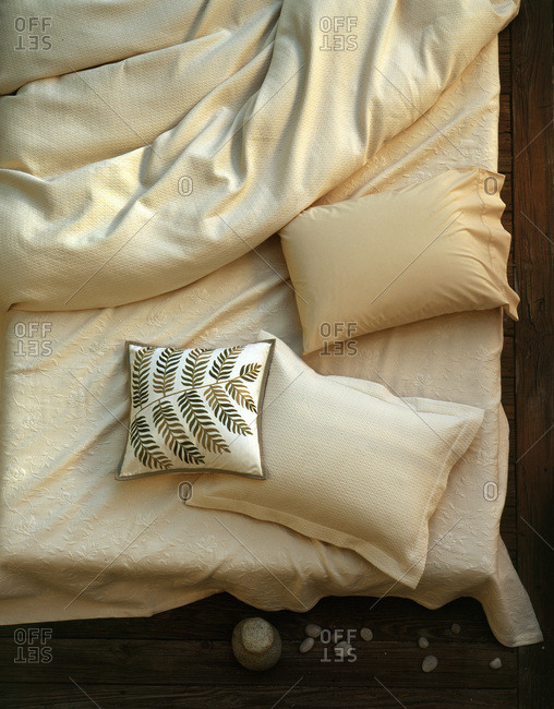 Off white sheets and pillows on bed seen from head and above with leaf pillow and small stones