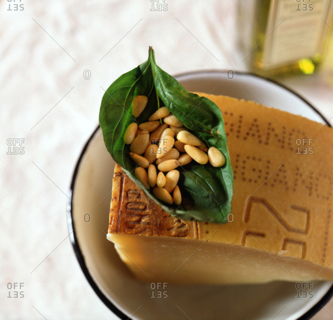 Pine nuts cradles inside large basil leaf on top of Parmigiano  Reggiano piece. Olive oil in background.