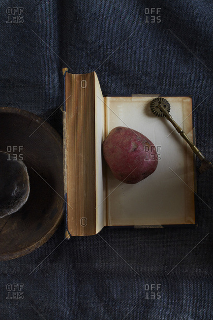 Single red potato on open book with brass object and two wooden bowls on blue fabric
