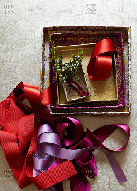 Collections of red and violet ribbons with juniper berries in small boxes