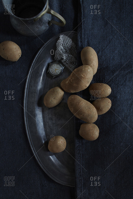 Potatoes strewn across oval pewter platter with pewter jug and chain link bracelet and watch on blue, navy cloth