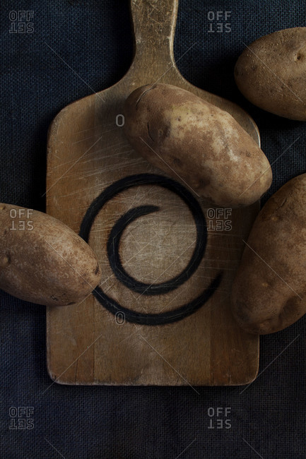 Russet potatoes on cutting board that has burn ring on blue cloth