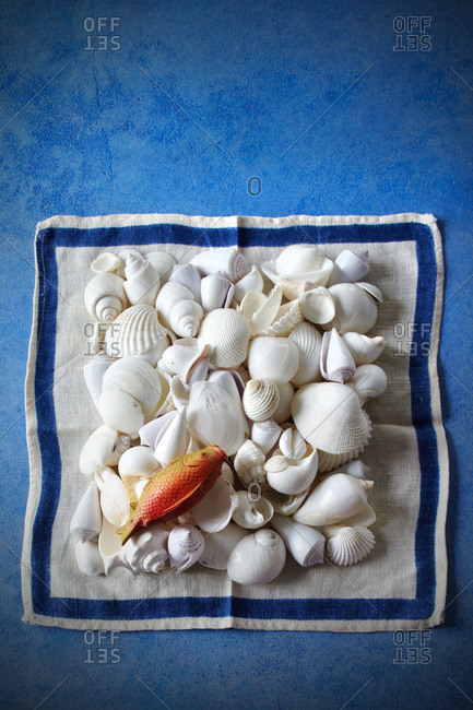 A pile of white shells on white handkerchief with blue strip and plastic goldfish on blue table