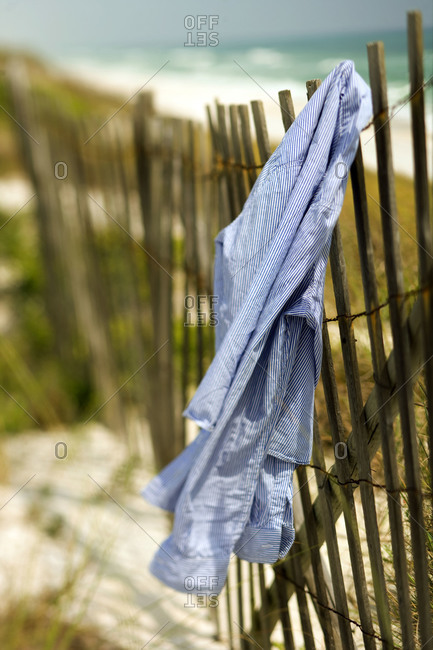 Blue and white striped shirt on hurricane fencing in dunes on beach in Florida